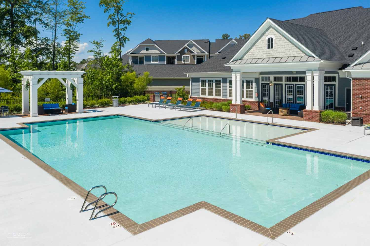 Pool with shallow sundeck, patio lounge chairs, and clubhouse access.